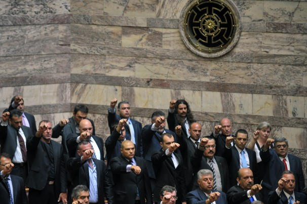 Golden Dawn members give a raised-fist salute as they are sworn into parliament. Louisa Gouliamaki / AFP via Getty Images