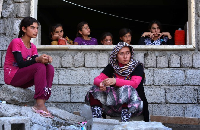 "Iraqi Yazidi women who fled the violence in the northern Iraqi town of Sinjar, sit at a school where they are taking shelter in the Kurdish city of Dohuk in Iraq's autonomous Kurdistan region, on August 5, 2014. Islamic State (IS) Sunni jihadists ousted the Peshmerga troops of Iraq's Kurdish government from the northern Iraqi town of Sinjar, forcing thousands of people from their homes. The Yazidis, are a small community that follows a 4,000-year-old faith and have been repeatedly targeted by jihadists who call them ""devil-worshipers"" because of their unique beliefs and practices. AFP PHOTO/SAFIN HAMED (Photo credit should read SAFIN HAMED/AFP/Getty Images)"